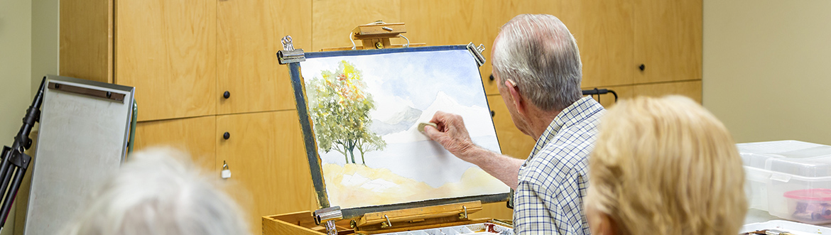 senior painting in an art studio